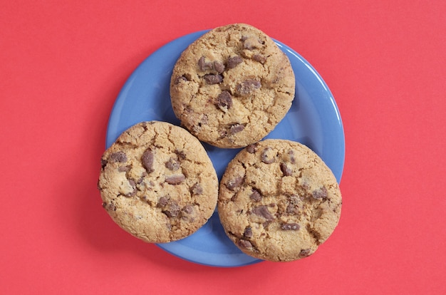 Biscuits aux pépites de chocolat sur une plaque bleue sur fond rouge