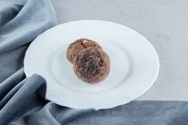 Biscuits aux pépites de chocolat sur un plateau blanc à côté de nappe sur fond de marbre.