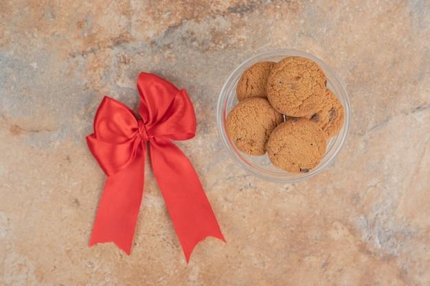 Biscuits aux pépites de chocolat avec ruban sur fond de marbre.