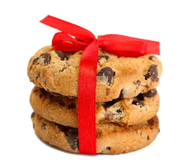 Biscuits aux pépites de chocolat avec ruban rouge isolé sur une surface blanche