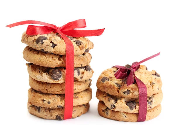 Biscuits aux pépites de chocolat avec des rubans rouges isolés sur blanc