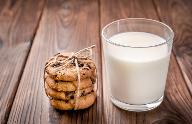 Biscuits aux pépites de chocolat et verre de lait sur bois.
