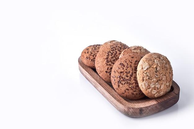 Biscuits à l'avoine et au cumin dans un plateau en bois sur blanc.