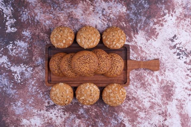 Biscuits à l'avoine au cumin noir sur un plateau en bois au centre.
