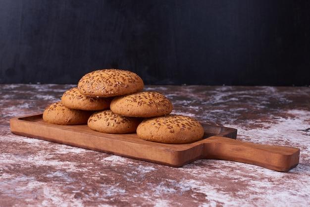Biscuits à l'avoine au cumin noir sur un plateau en bois à travers le marbre.