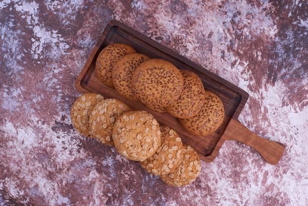 Biscuits à l'avoine au cumin noir sur un plateau en bois, vue du dessus.