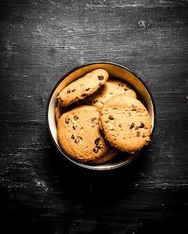 Biscuits à l'avoine dans un bol. sur une table en bois noire.