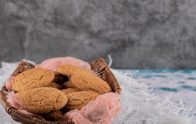 Biscuits à l'avoine dans un panier en bois sur un torchon rose.