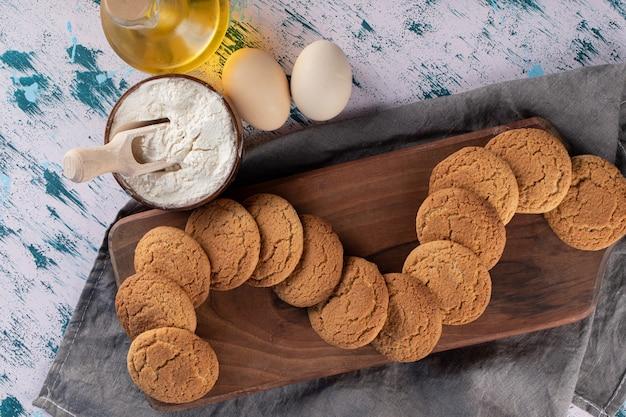 Biscuits à l'avoine dans un plateau en bois avec des ingrédients autour.