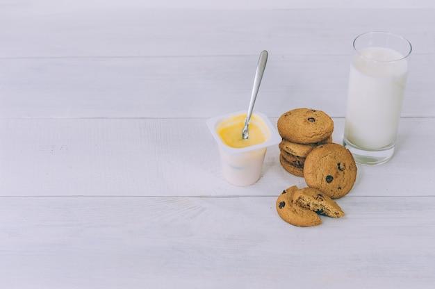 Biscuits à l'avoine avec du chocolat sur un espace lumineux avec un verre de lait et de yaourt.