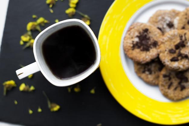 Biscuits à l'avoine avec du chocolat sur une plaque jaune vif et une tasse de café