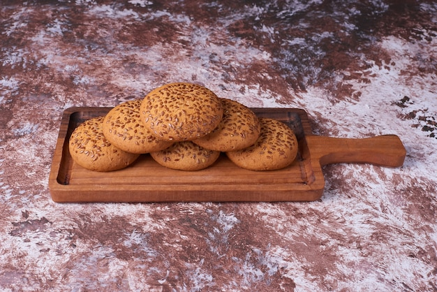 Biscuits à l'avoine avec du cumin noir sur un plateau en bois, vue d'angle.