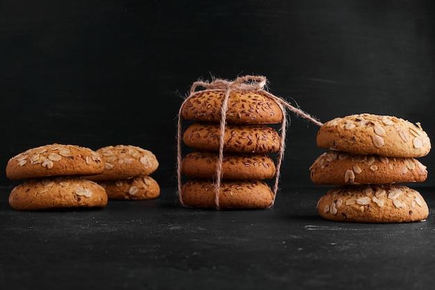 Biscuits à l'avoine avec du cumin noir sur une surface noire.