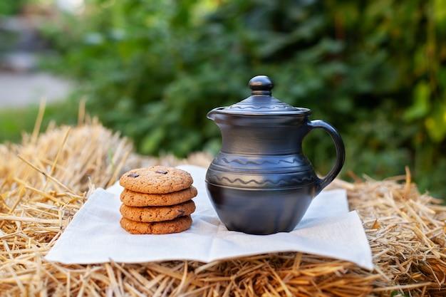 Biscuits à l'avoine faits maison avec cruche d'argile sur la paille dans le champ.
