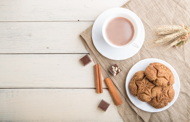 Biscuits à l'avoine faits maison avec une tasse de cacao sur un fond en bois blanc. vue de dessus, espace copie.
