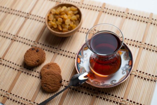 Biscuits à l'avoine faits maison avec une tasse de thé et un bol de raisins secs