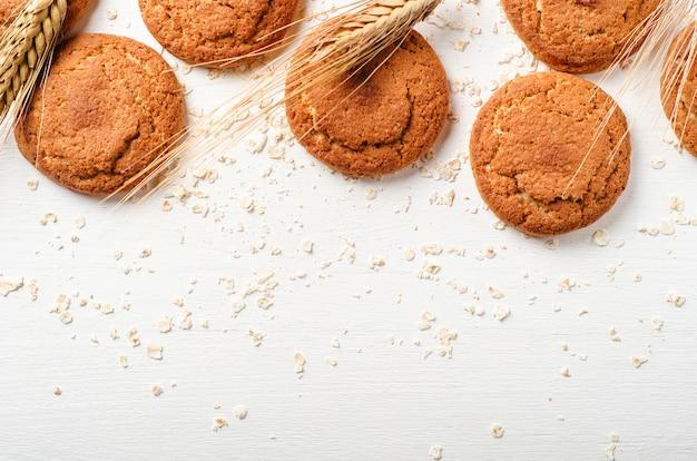 Biscuits à l'avoine avec des flocons d'avoine et des épillets sur un fond en bois blanc.