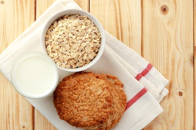 Biscuits à l'avoine avec flocons d'avoine et tasse de lait sur la table en bois se bouchent