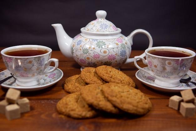 Biscuits à l'avoine à grains entiers avec une tasse de thé et de sucre sur une table en bois.