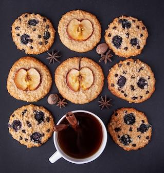 Biscuits à l'avoine avec des pommes et du café sur une vue de dessus de fond sombre