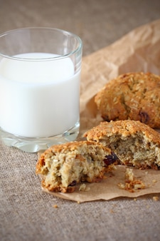 Biscuits à l'avoine avec des raisins secs cassés avec des miettes et un verre de lait sur du papier d'emballage et sur une nappe grise brute.