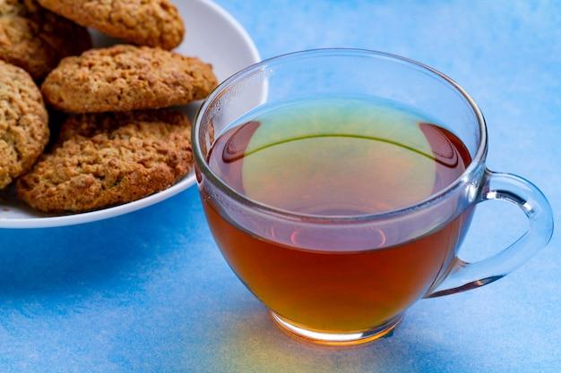 Biscuits à l'avoine et une tasse de thé sur une surface bleue. farine, dessert aux céréales et boisson chaude
