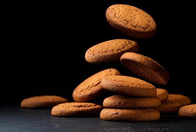 Biscuits à l'avoine tombant sur fond noir