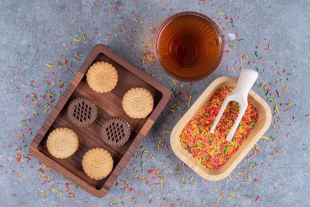 Des biscuits, un bol de bonbons et une tasse de thé