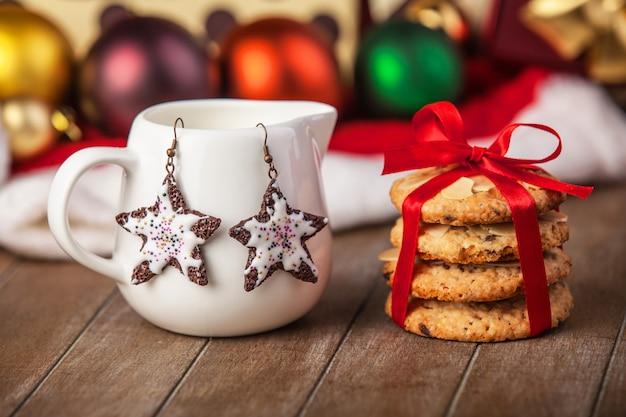Biscuits, boucles d'oreilles et cadeaux de noël à l'arrière-plan