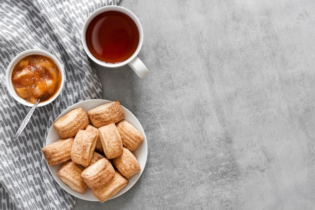 Biscuits à la cannelle sucrés faits maison, tasse de thé et confiture de pommes vue de dessus sur fond gris