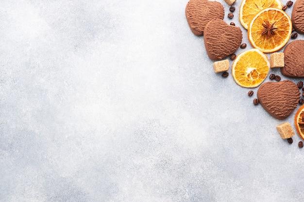 Biscuits coeur au chocolat, oranges, cannelle et épices épicées sur une table grise, vue du dessus, copiez l'espace.