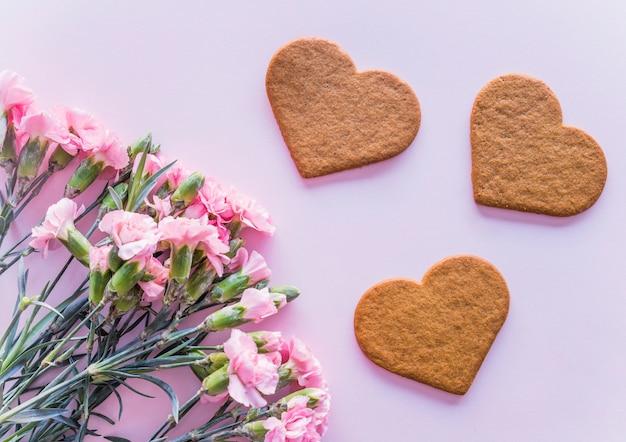 Biscuits de coeur avec des fleurs sur la table