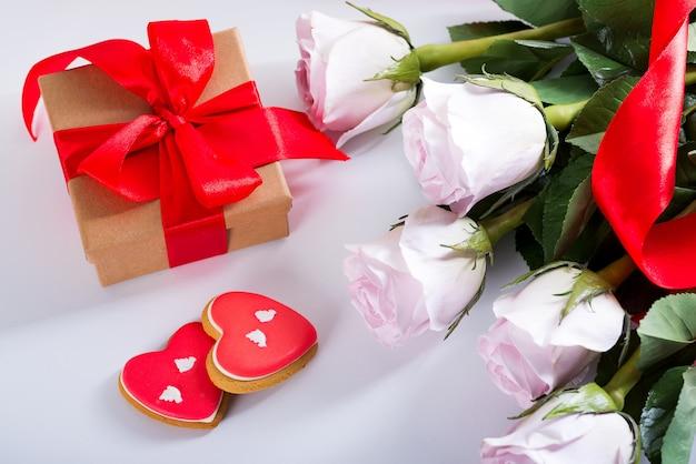 Biscuits coeur saint valentin fait maison, roses roses et coffret rouge sur tableau blanc