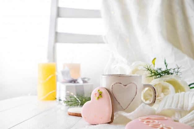 Biscuits de coeur avec une tasse de café sur un fond en bois avec plaid, espace copie