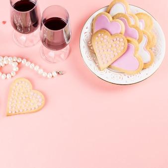 Biscuits coeur, verres à vin et vin sur rose pastel