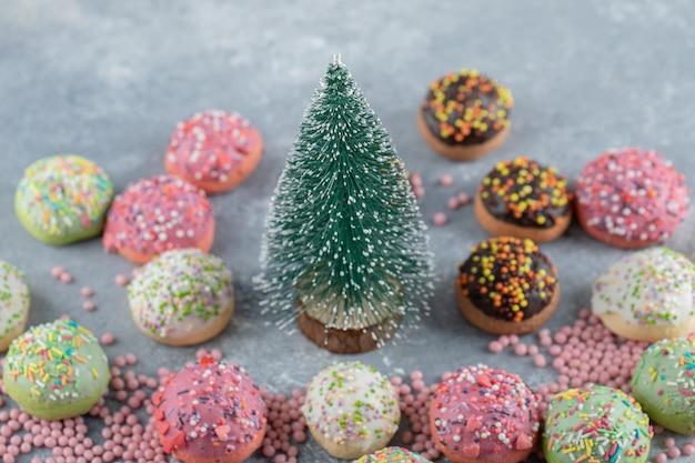 Biscuits colorés décorés de paillettes autour du pin.