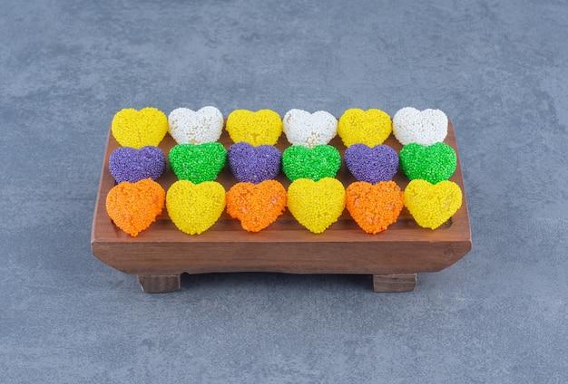 Biscuits colorés sur le plateau, sur le fond de marbre.