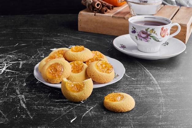 Biscuits à la confiture d'abricots avec une tasse de thé.