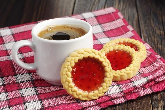 Biscuits avec confiture et tasse de café chaud sur une nappe rouge secrète de table en bois