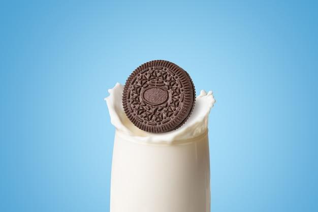 Biscuits et crème de saveur de chocolat tombés dans des éclaboussures de lait frais sur fond bleu