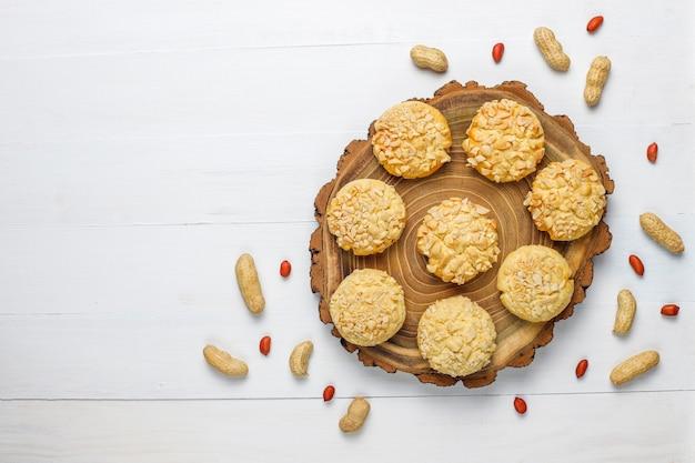 Biscuits croquants faits maison avec des arachides sur une table en bois blanc