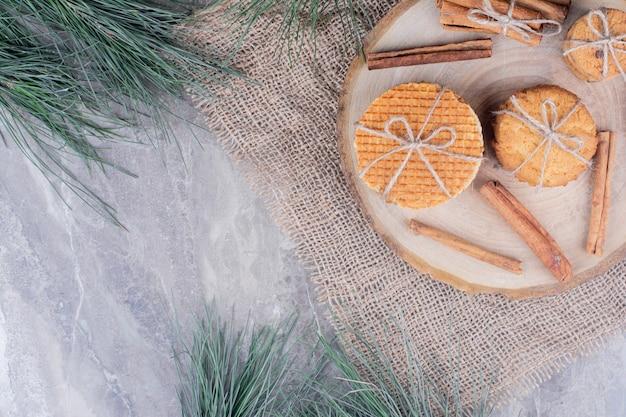 Biscuits croustillants sur une planche de bois avec des bâtons de cannelle autour