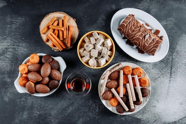 Biscuits dans des assiettes et bol avec roulade, gaufres vue de dessus sur une texture noire