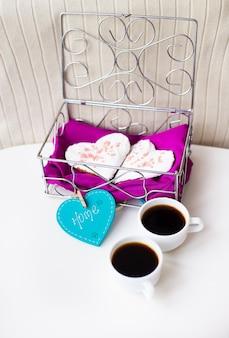 Des biscuits dans un cœur et deux tasses de café sur la table qui dit maison