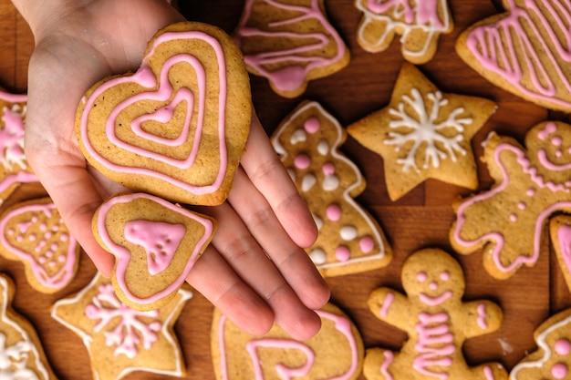 Biscuits de deux coeurs avec décoration pour la saint valentin entre les mains de la femme
