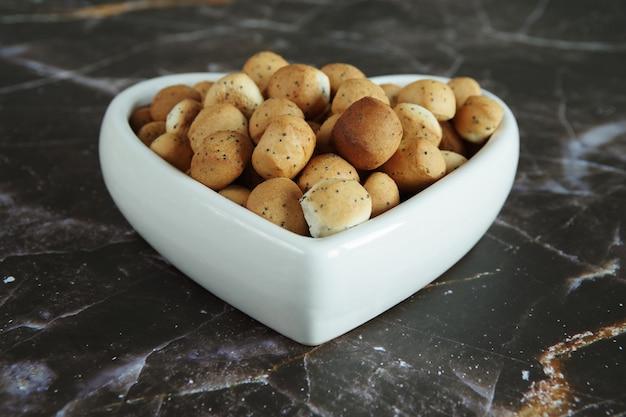 Biscuits du réveillon de noël kuciukai sur fond marron kuciukai sont servis pendant le dîner du réveillon de noël en lituanie et sont consommés avec du lait de pavot
