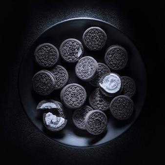 Biscuits élégants noirs dans une assiette ronde