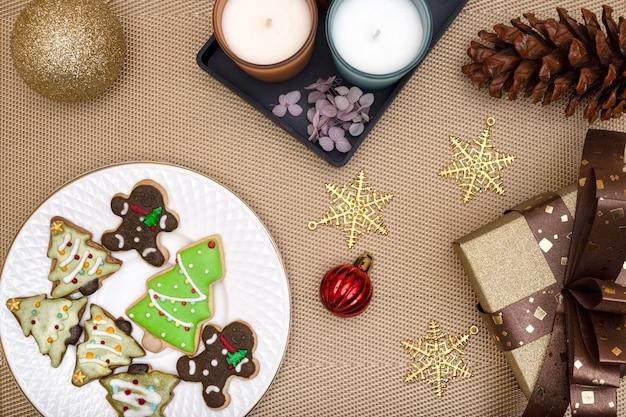 Biscuits enrobés de sucre et biscuits à thème de noël avec bougies parfumées et décorations de noël.