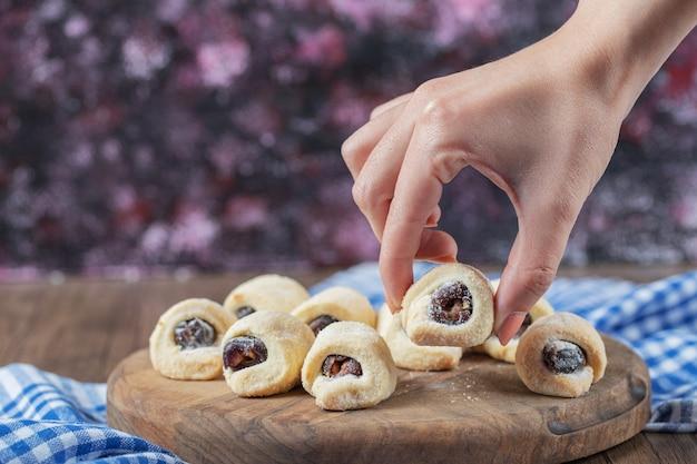 Biscuits enveloppants traditionnels avec confiture de fraises sur une planche de bois.
