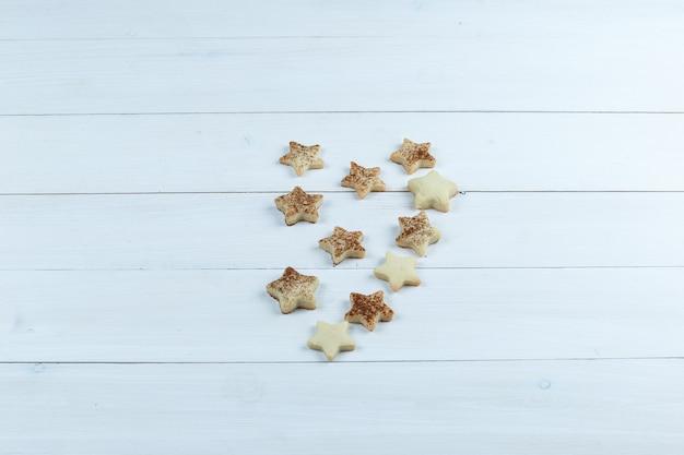 Biscuits étoilés sur fond de planche de bois blanc. vue grand angle.